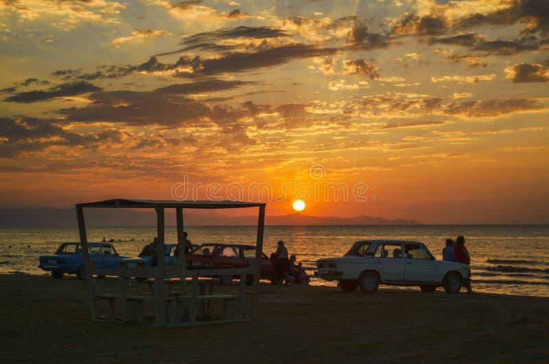 A paisagem de ardência bonita do por do sol no mar Cáspio e no céu alaranjado acima dela com reflexão dourada do sol impressionan imagens de stock