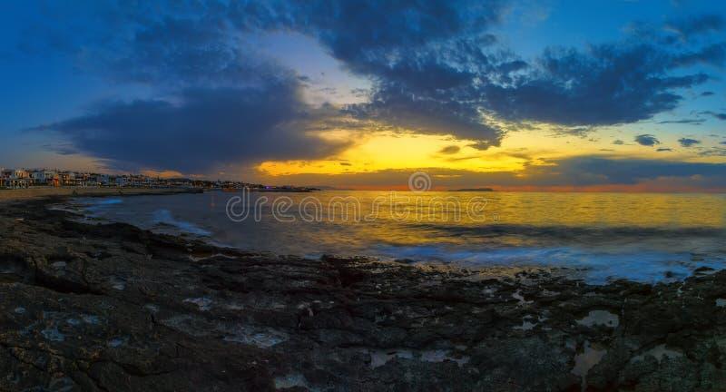 Paisagem de ardência bonita do por do sol no mar com baía e estância turística com hotéis e no céu alaranjado acima dele com sol  imagem de stock royalty free