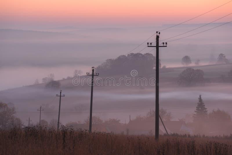 Paisagem de Autumn Country Linha elétrica na névoa no nascer do sol fotos de stock