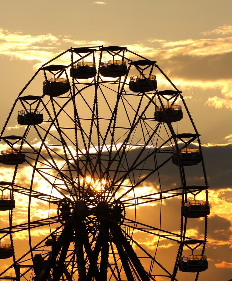 Paisagem de Ferris Wheel com o ajuste do sol atrás dele imagem de stock