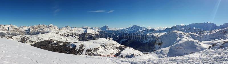 A paisagem de montanhas cobertos de neve e as inclinações de uma estância de esqui em cumes italianos fotografia de stock royalty free