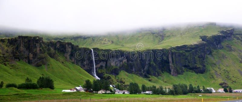 Paisagem de penhascos espetaculares com cachoeiras e de explorações agrícolas em Islândia do sul em um dia nebuloso foto de stock