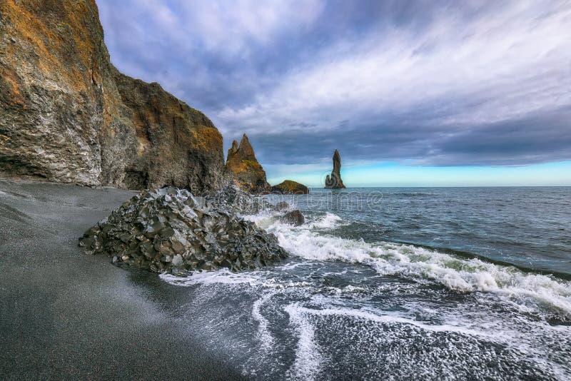 A paisagem de surpresa com formações de rocha do basalto pesca à linha os dedos do pé na praia preta Reynisfjara perto da vila de imagens de stock