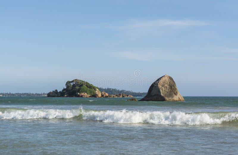 Paisagem de surpresa do oceano na praia tropical bonita com as rochas na cidade de Weligama foto de stock royalty free