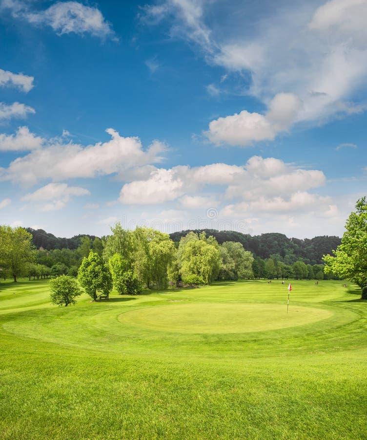 Paisagem do campo de golfe Coloque com grama verde, árvores, céu azul imagens de stock royalty free