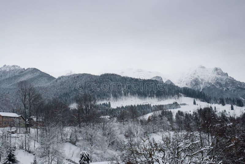 Paisagem do inverno Aldeia da montanha no farelo, Romanian Carpathians fotografia de stock