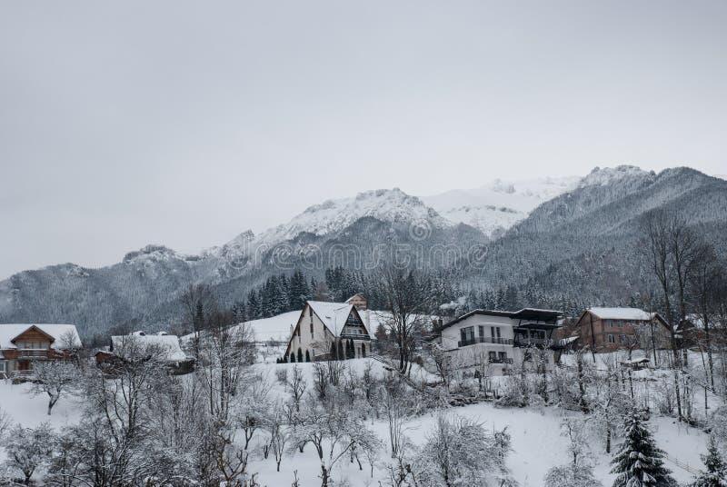 Paisagem do inverno Aldeia da montanha no farelo, Romanian Carpathians foto de stock royalty free