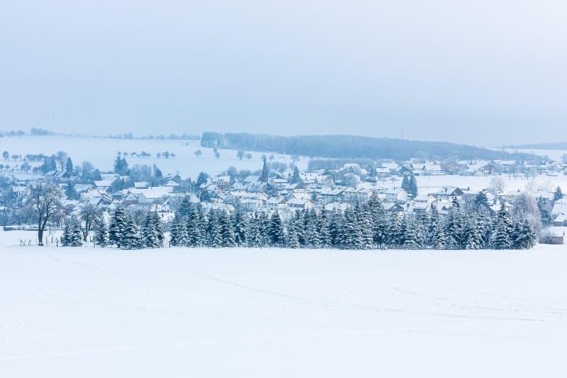 A paisagem do inverno com as árvores cobertas com a geada e uma vila europeia pequena é ficada situada entre os campos cobertos d imagem de stock royalty free