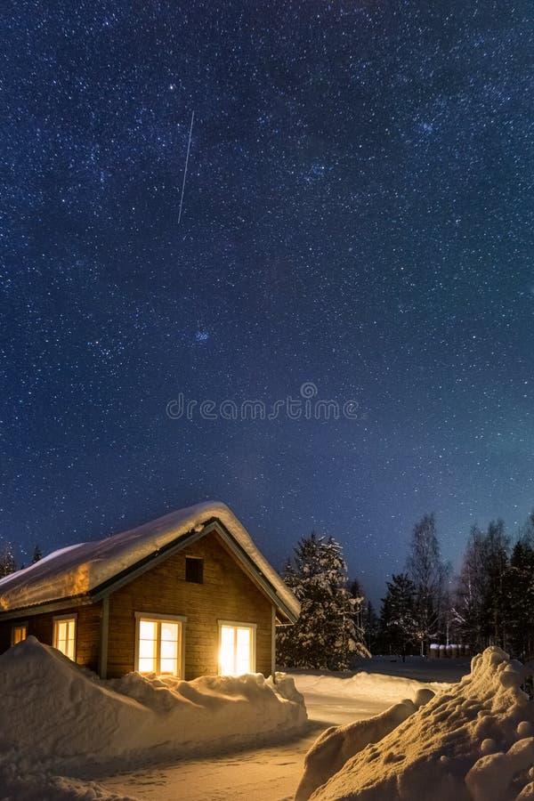 Paisagem do inverno com casa de madeira sob um céu estrelado bonito foto de stock royalty free
