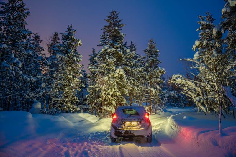 Paisagem do inverno com condução automobilístico na noite fotos de stock royalty free