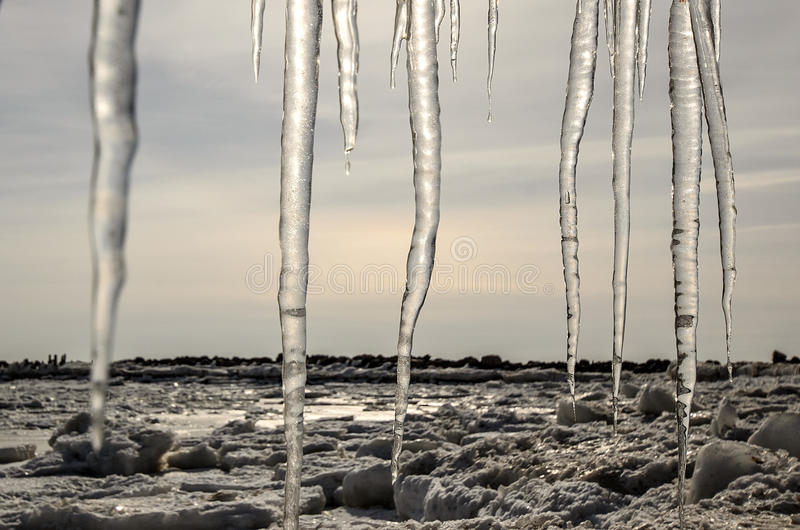 Paisagem do inverno com a costa de mar, gelo e sincelos congelados imagens de stock