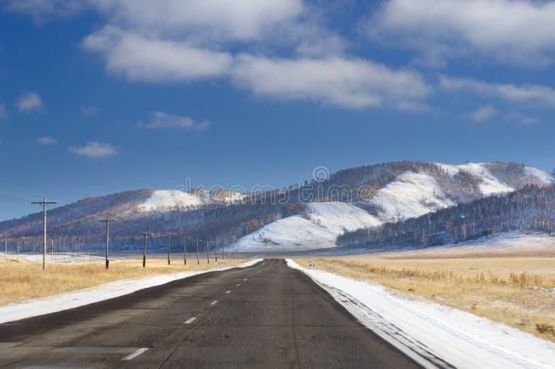 Paisagem do inverno com a estrada asfaltada através do campo agrícola limpado aos montes cobertos com as árvores e a neve desenca imagens de stock