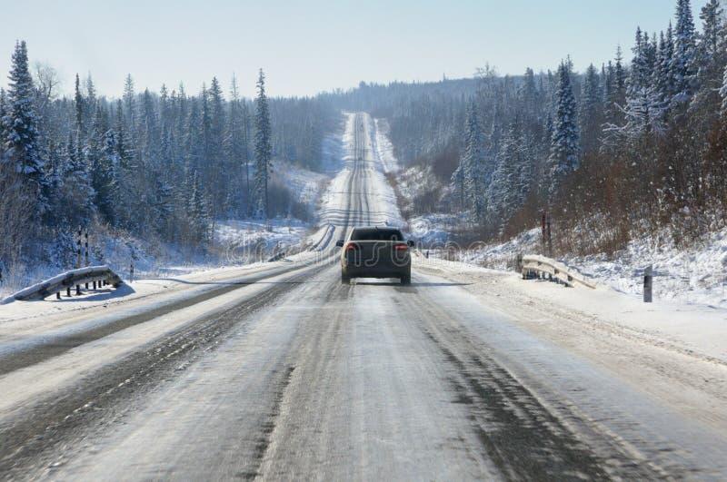 Paisagem do inverno com a estrada gelada do alcatrão nos montes lisos cobertos com a floresta nevado no inverno imagem de stock royalty free