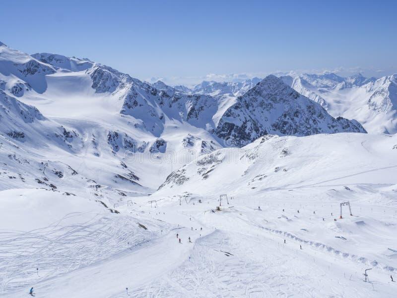 Paisagem do inverno com inclinações de montanha cobertos de neve e pistas com os esquiadores que apreciam o dia ensolarado da mol fotografia de stock royalty free