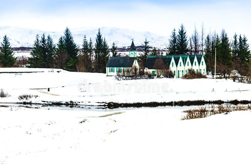 Paisagem do inverno da igreja e de casas de madeira pequenas no parque nacional de Thingvellir, Islândia fotos de stock royalty free