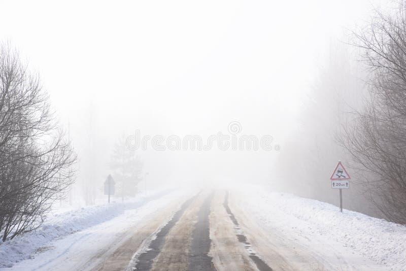 Paisagem do inverno da neve Estrada vazia na névoa e no ro escorregadiço do russo imagens de stock