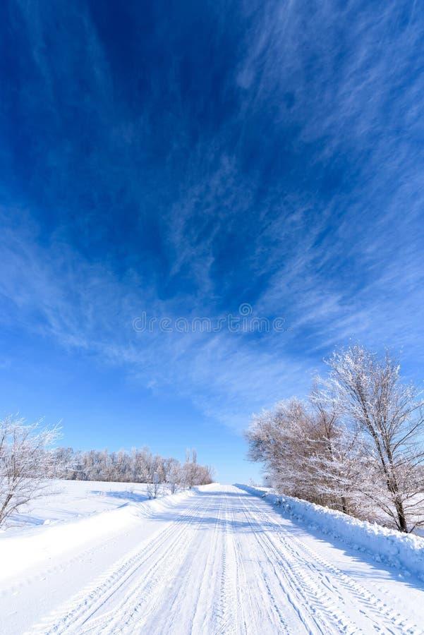 Paisagem do inverno estrada nevado branca, céu azul, árvores cobertas com a geada imagens de stock