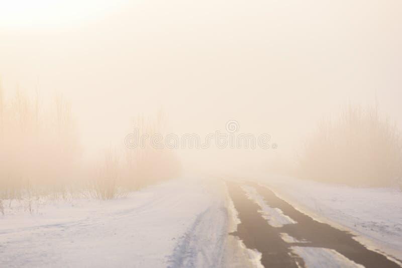 Paisagem do inverno Estrada secundária vazia na névoa da manhã imagem de stock