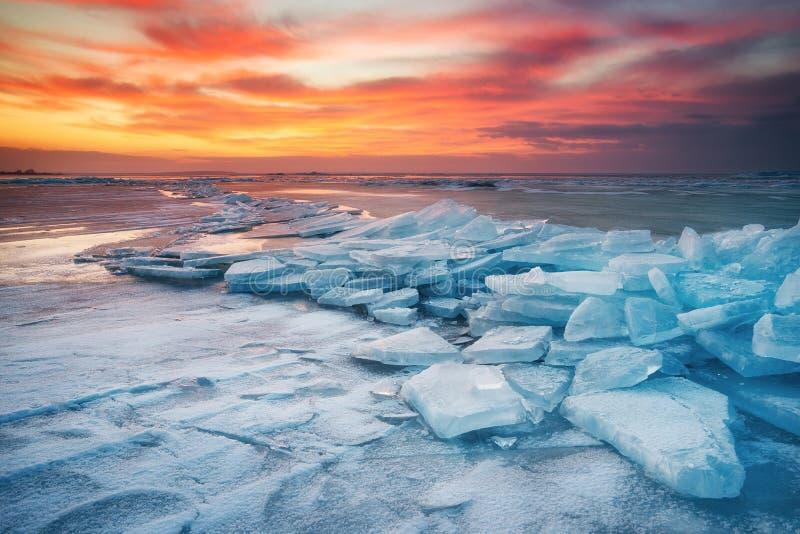 Paisagem do inverno no litoral durante o por do sol Consoles de Lofoten, Noruega Gelo e céu do por do sol foto de stock royalty free