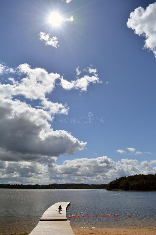 Paisagem do lago com ponte de madeira e sol imagens de stock