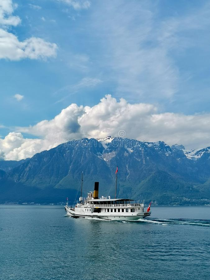 Paisagem do lago Genebra e de cumes suíços com la Suisse do barco de CGN na posição intermediária imagens de stock