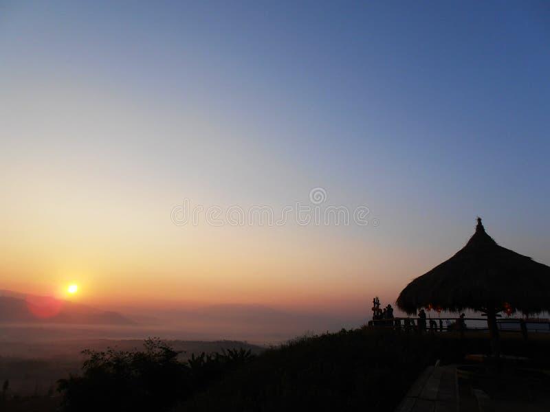 Paisagem do nascer do sol com o pavilhão do telhado da grama imagem de stock royalty free
