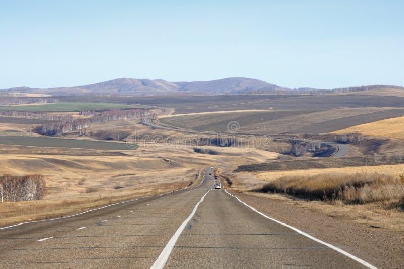 Paisagem do outono com a estrada do alcatrão ao horizonte entre os montes lisos cobertos com a grama amarela seca e campos agríco imagem de stock