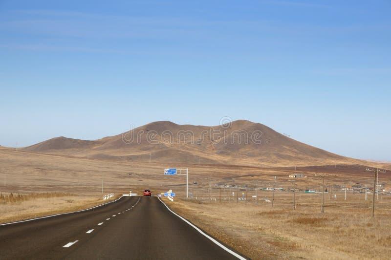 Paisagem do outono com a estrada do alcatrão ao horizonte entre os montes lisos cobertos com a grama amarela seca sob o céu azul fotos de stock royalty free