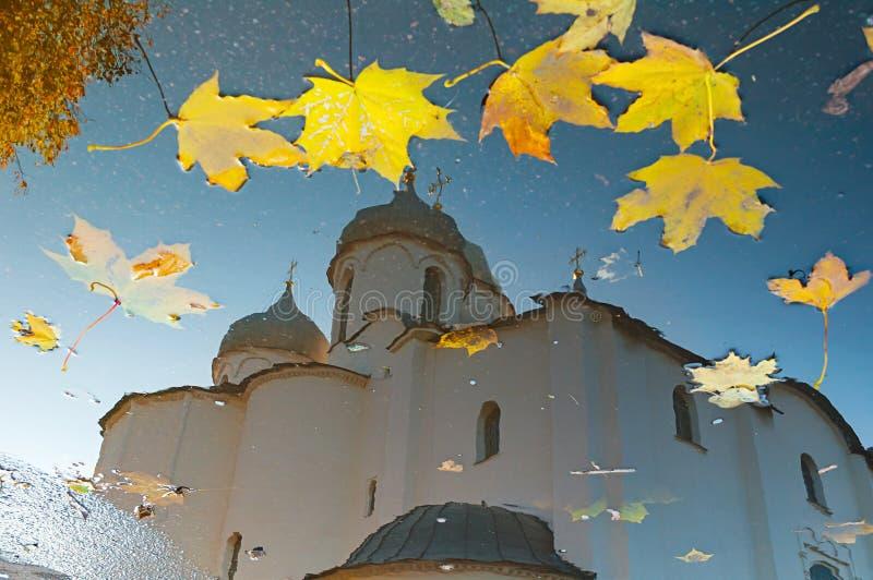 Paisagem do outono - reflexão em uma poça da catedral do St Sophia quadro pelas folhas de outono em Veliky Novgorod, Rússia foto de stock royalty free