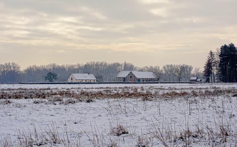 Paisagem do pântano e da floresta do inverno com a exploração agrícola velha na luz do evenng imagem de stock