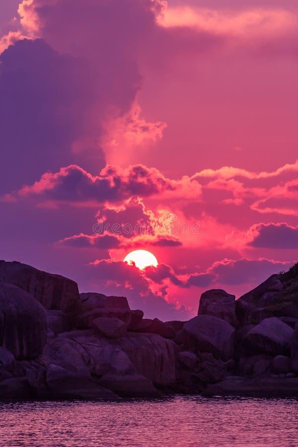 Paisagem do por do sol com o céu dramático no fundo com ilha e mar da rocha fotos de stock