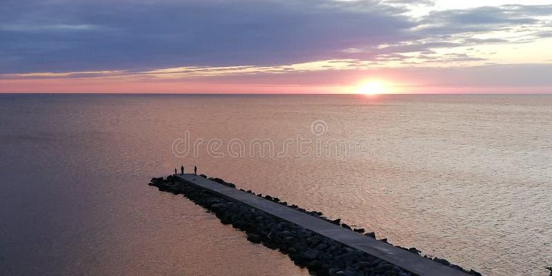 Paisagem do por do sol da noite do mar nas cores do rosa, as azuis e as roxas Silhuetas dos povos na alameda Fundo fotografia de stock