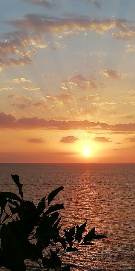 Paisagem do por do sol do mar Os raios do sol de ajuste perfuram as nuvens foto de stock royalty free