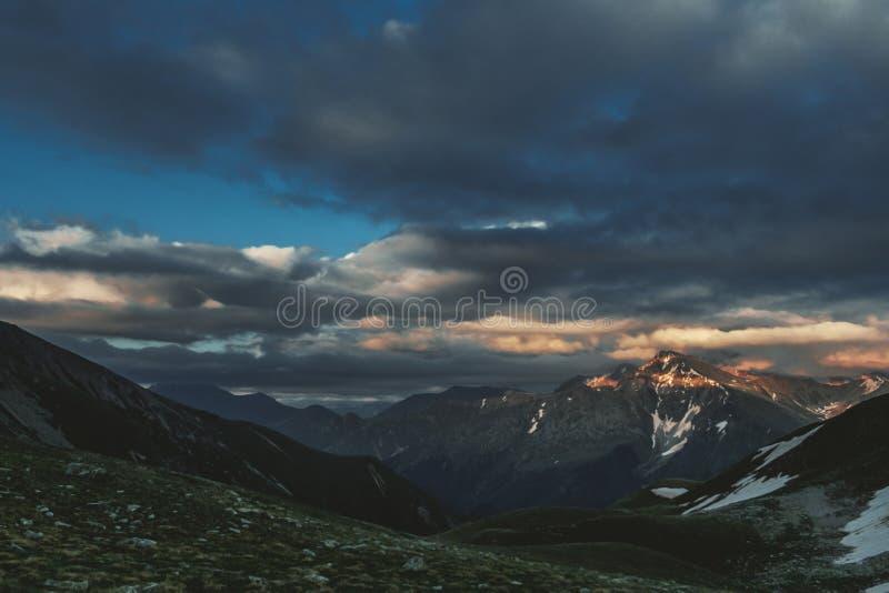 Paisagem do por do sol do pico de montanha com principalmente o céu nebuloso dramático sombrio e feixes alaranjados e vermelhos d imagem de stock royalty free