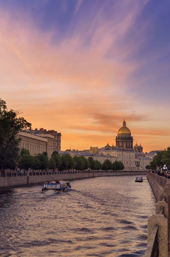 Paisagem do por do sol do ver?o de St Petersburg, R?ssia Saint Isaac Cathedral atrav?s do rio de Moyka Barcos de prazer no fotos de stock
