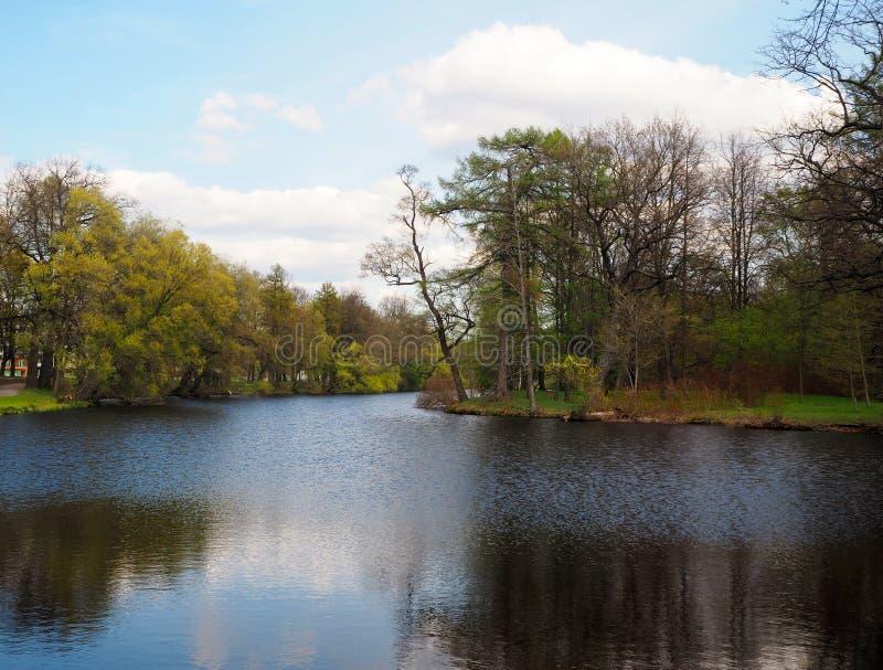 A paisagem do rio corre através do parque com as árvores verdes amarelas e o céu azul fotos de stock