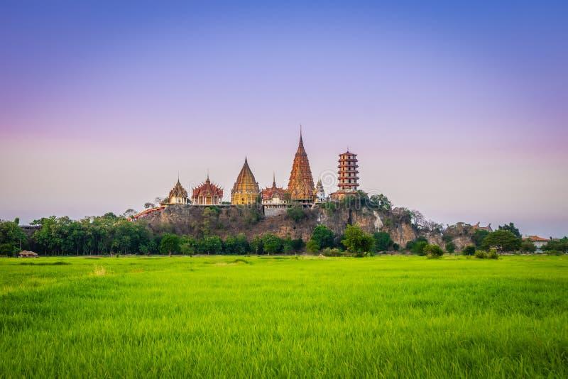 Paisagem do templo da caverna de Wat Tham Sua Temple Tiger no scence do por do sol com campos do arroz do jasmim na província de  imagem de stock