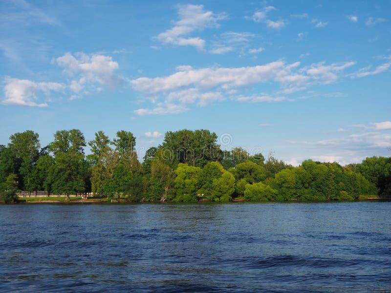 Paisagem do verão com as árvores verdes que estão no banco de um rio largo e de um céu azul fotografia de stock royalty free