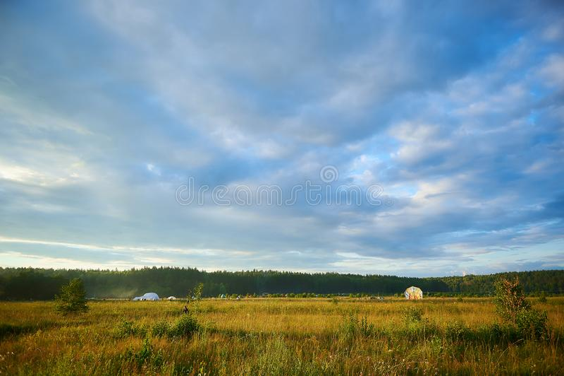 Paisagem do verão com campo, o céu nebuloso azul e um acampamento, ângulo largo imagens de stock