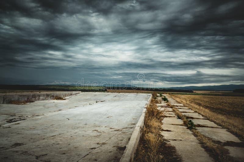 A paisagem do verão com nuvens de tempestade e campo de trigo após a colheita Sun irradia sobre o lugar do armazenamento do campo imagem de stock royalty free