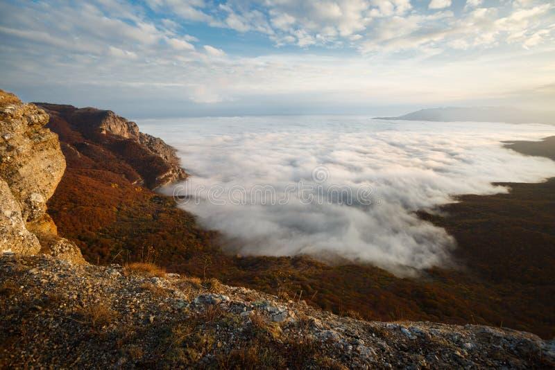 Paisagem dramática do por do sol em montanhas altas amarelas do outono sobre nuvens Cenário bonito do céu imagem de stock royalty free