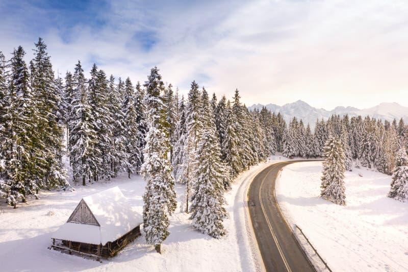 Paisagem fantástica do inverno com casa e a estrada de madeira em montanhas nevados fotografia de stock