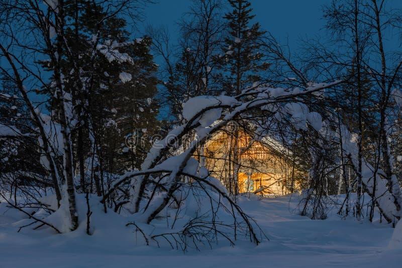 Paisagem fria da noite do inverno, casa de madeira pequena com luz morna imagens de stock