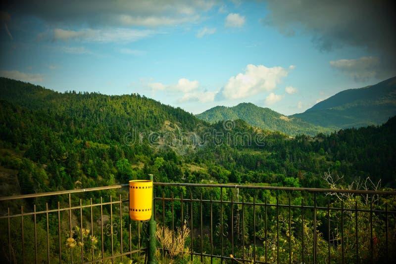 Paisagem grega da montanha com balde do lixo amarelo foto de stock royalty free