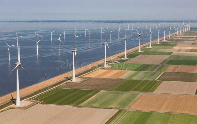 Paisagem holandesa da vista aérea com as turbinas eólicas a pouca distância do mar ao longo da costa imagens de stock royalty free