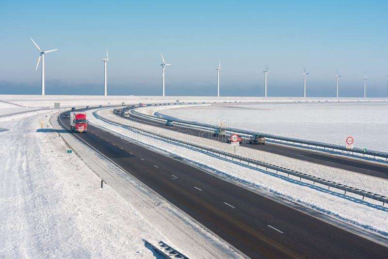 Paisagem holandesa do inverno com a estrada ao longo das turbinas eólicas fotografia de stock royalty free