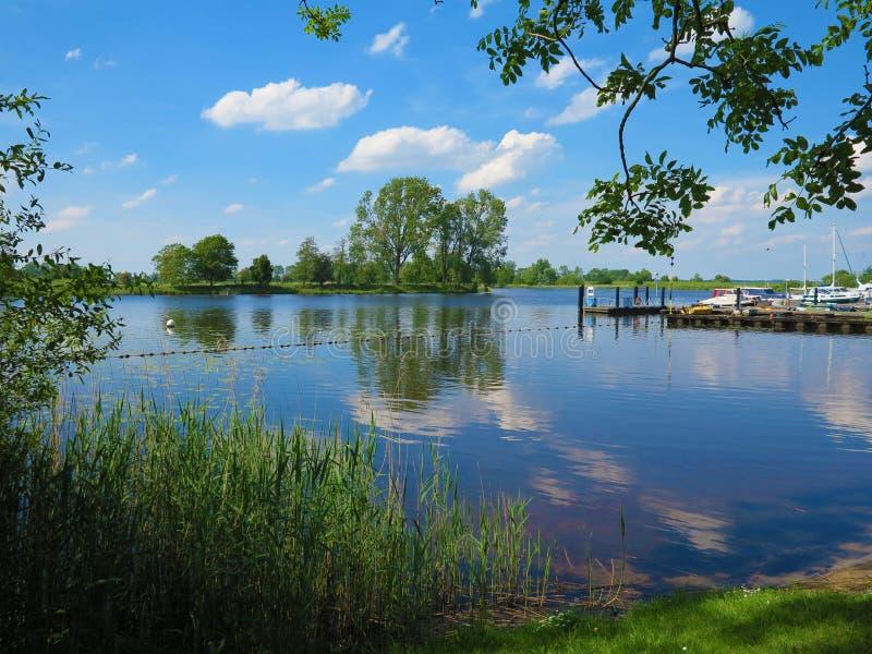 Paisagem idílica rural com o rio Eider e a pequena marina de pechincha em Schleswig-Holstein imagem de stock