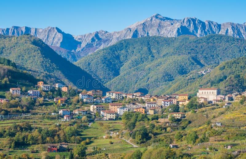 Paisagem idílico com a vila de Poggio e os cumes de Apuan no fundo Província de Lucca, Toscânia, Itália central fotos de stock