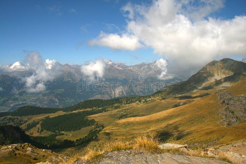 Paisagem idílico do verão com as nuvens nos cumes fotografia de stock royalty free