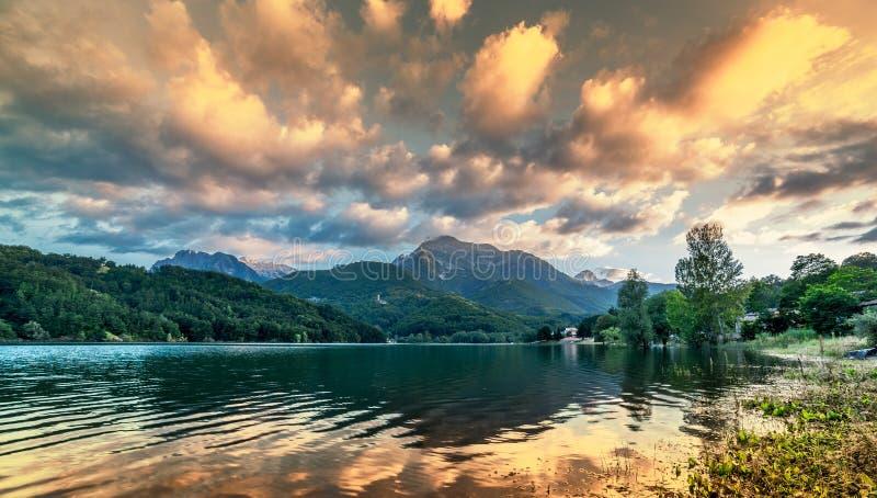 Paisagem intensa vibrante do por do sol no fundo do lago e da montanha fotos de stock